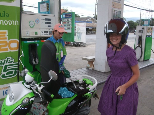 Amy gets gas for her bike.  How cute she looks in her helmet!