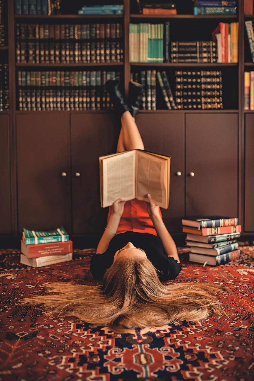 woman lying on area rug reading books