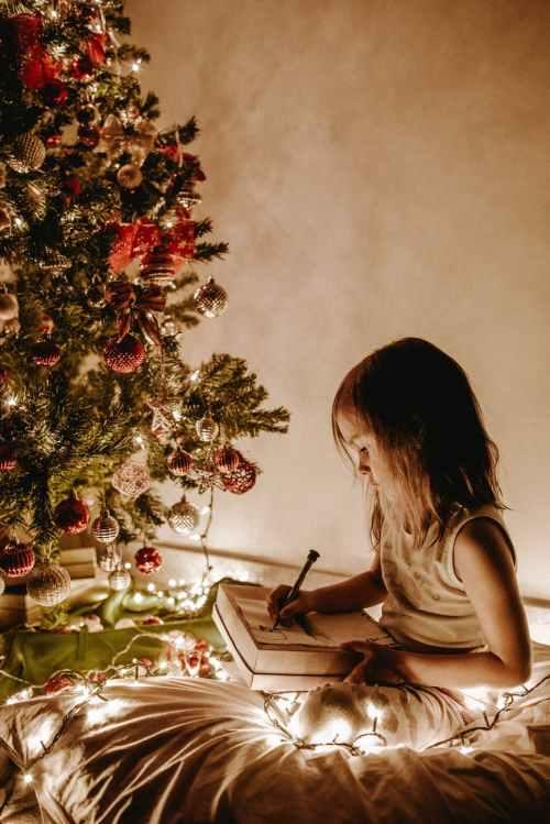 photo of girl sitting near christmas tree